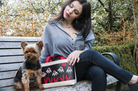 Woman and a dog sitting on a park bench together