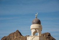 Top of Mosque with Golden Moon Crescent against Blue Sky and Mountains near Wadi Bani Khalid, Oman