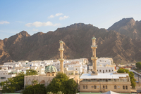 Cityscape with Two Towers of Mosque with Mountains in the background, Muscat, Oman