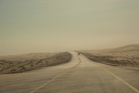 Car in the Distance on Highway during Sand Storm south towards Salalah, near Sharkh, South Oman, Oman