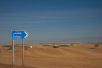 Road Sign in Desert for Jishayr with Huts Covered with Plastic, Jishayr, South Oman, Oman