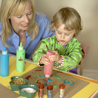 Mother sitting with young daughter creating art work, arts and crafts at home