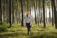 Portrait of Young Woman Collecting Mushrooms in Scots Pine (Pinus sylvestris) Forest in Early Autumn, Bavaria, Germany