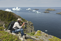 Hiker Photographing Icebergs from Clifftop, Lower Head Trail near Long Point Lighhouse, Twillingate Island, Newfoundland, Canada