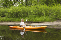 Mature Woman Kayaking on River in Spring, Moira River near Madoc, Ontario, Canada