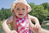 Baby girl wearing sunhat oudoors, looking at camera and crying, USA