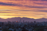 Skyline of downtown Santiago de Chile at sunset with Telefonica Building in center and Andes mountains in the background, Santia
