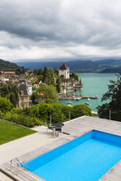 Blue swimming pool in front of Oberhofen Castle at Lake Thun with thunderstorm clouds, Canton of Bern, Switzerland