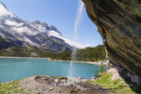 Beneath a waterfall cascading in front of Lake Oeschinensee within the Bernese Alps, mountains above Kandersteg, UNESCO World He