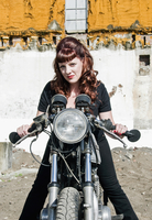 A red haired woman standing with a cafe racer style motorcycle.
