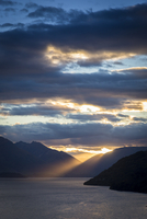 Scenic view of silhouetted mountains and ocean at sunset, Queenstown, Otago, South Island, New Zealand