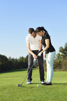 Man Showing Woman how to Play Golf on Golf Course in Autumn, Bavaria, Germany