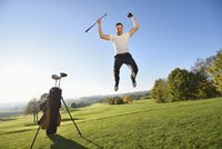 Golfer Jumping in the Air on Golf Course in Autumn, Bavaria, Germany
