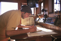 Man makes Entry into Log Book aboard Schooner, Tree of Life