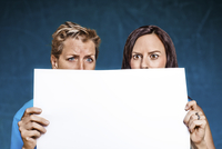 Two Women holding Piece of Paper in front of their Faces with Surprised Look, Studio Shot