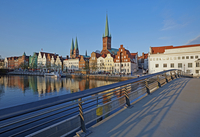 Cityscape of Lubeck Old Town, over canal with footbridge and twin spires of St Mary's church and spire of St Peter's church illu