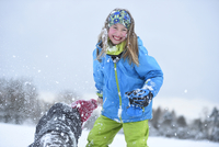 Close-up of two girls playing in the snow havng a snowball fight, winter, Bavaria, Germany
