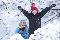 Portrait of two girls playing in the snow, winter, Bavaria, Germany