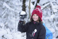 Close-up of a girl playing in the snow holding snowball, winter, Bavaria, Germany