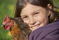Close-up of Happy Girl with Chicken (Gallus gallus domesticus) in Spring, Upper Palatinate, Bavaria, Germany