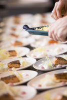 Close-up of Chef Garnishing Plates of Salmon