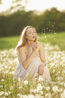 Young woman sitting in a withered dandelion meadow in spring, Germany