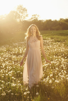Young woman standing in a withered dandelion meadow in spring, Germany