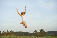 Young woman jumping in the air on a meadow in spring, Germany