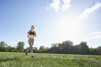 Young woman exercising, running in a park in spring, Bavaria, Germany