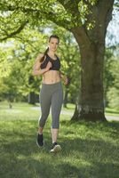 Close-up of a young woman exercising, running in a park in spring, Bavaria, Germany