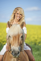 Young woman riding a haflinger horse in spring, Bavaria, Germany