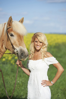 Young woman standing beside a haflinger horse in spring, Bavaria, Germany