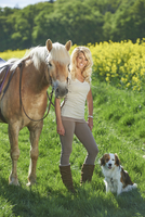 Young woman with a kooikerhondje dog standing beside a haflinger horse in spring, Bavaria, Germany