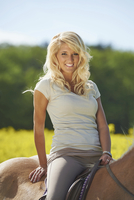 Close-up portrait of a young woman sitting on a Haflinger horse in spring, Bavaria, Germany
