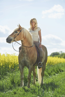 Young woman sitting on a Haflinger horse in spring, Bavaria, Germany