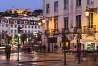 View of the hilltop fortification Castelo de Sao Jorge from an illuminated street corner at Praca Dom Petro IV (Rossio), blue ho