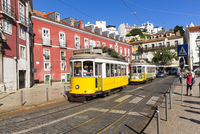 Old trams in front of colorful city buildings at Largo das Portas do Sol,  Alfama District, Lisbon, Portugal