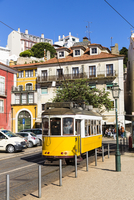 Old tram in front of colorful city buildings at Largo das Portas do Sol,  Alfama District, Lisbon, Portugal