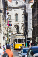 Traditional old tram on a crowded street in the historic city of Lisbon in the Baixa District, Lisbon, Portugal