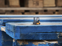 Toy figure driving toy forklift on wooden shipping pallets