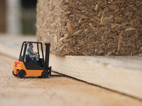 Close-up of toy figure driving toy forklift on wooden shipping pallets