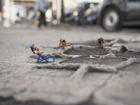 Close-up of miniature figures using tire treadmark and water as beach