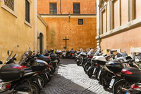 Line-up of parked scooters and cross on wall of building, Rome, Italy