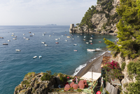 Scenic overview of fishing boats in the harbour and steep coastline with watchtower, Positano, Amalfi Coast, Campania, Italy