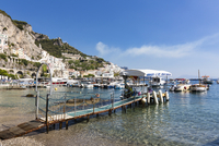 Small jetty for boat rentals on beach in front of the town of Amalfi, Amalfi Coast, Gulf of Salerno, Campania, Italy