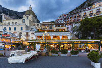 Boats on the beach in front of a restaurant with the Church of Santa Maria Assunta in the background at dusk, Positano, Amalfi C