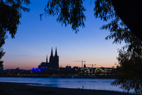Silhouetted Cologne Cathedral and River Rhine at dusk, Cologne, Germany