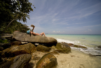 Back of young woman lying on rocks sunbathing and relaxing