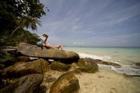 Back of young woman lying on rocks sunbathing and relaxing 20025324429| 写真素材・ストックフォト・画像・イラスト素材|アマナイメージズ