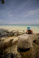 Young woman lying on rocks sunbathing and relaxing 20025324431| 写真素材・ストックフォト・画像・イラスト素材|アマナイメージズ